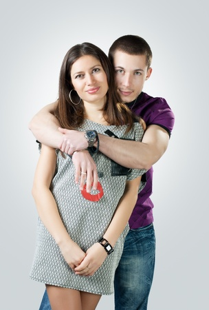 Portrait of romantic young couple over gray background. Stock Photo - 8441939