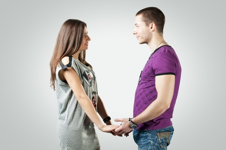 Portrait of romantic young couple over gray background. Stock Photo - 8441933