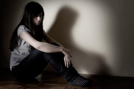 Depressed teenager girl sitting on floor. Stock Photo
