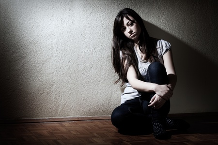 sad lonely girl: Depressed teenager girl sitting on floor. Stock Photo