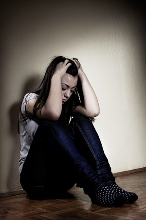 troubled teen: Depressed teenager girl sitting on floor. Stock Photo