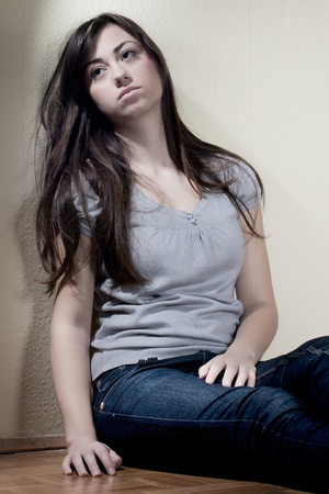 Depressed teenager girl sitting on floor. Stock Photo - 8548761