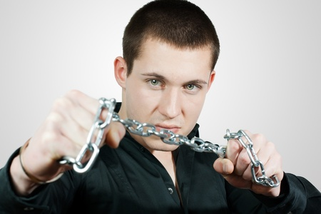 Young man wants to break the chains. Stock Photo - 8584772