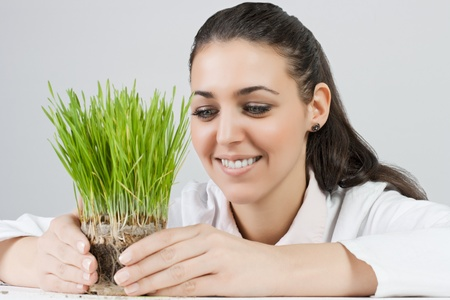 Portrait of business woman protects green plant. photo