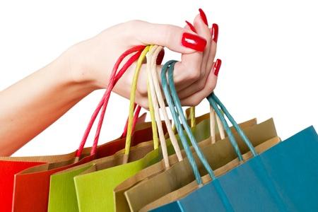 Manos femeninas mantienen colorida bolsa de compras. Foto de archivo