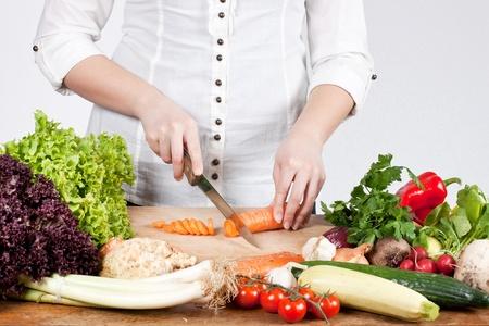 nutrici�n: Mujer cortar zanahorias con verduras mixtas.