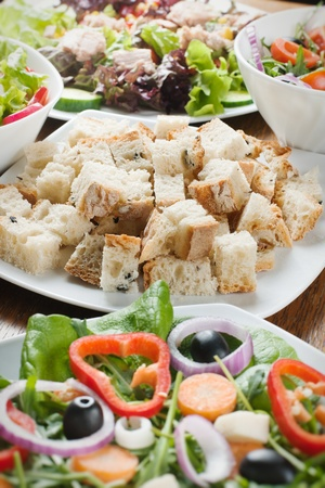 Pieces of fresh bread and salad setting on table. photo