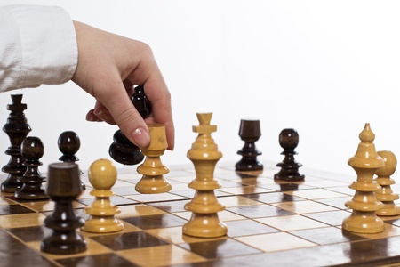 strategy decisions: Human hand move chess figure at chessboard. Stock Photo