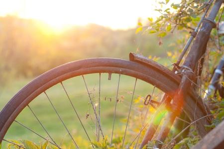 Oude fiets bij zonsondergang.