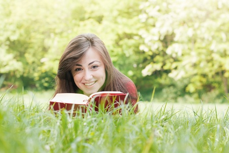Portrait of happy student relaxed outdoors reading book. Stock Photo - 9582455
