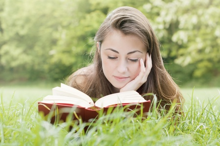 cute teen girl: Portrait of happy student relaxed outdoors reading book.