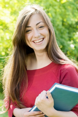 Portrait of happiness student outdoors with book. Stock Photo - 9582519