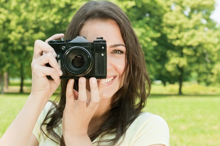Woman taking photo with old fashioned camera. photo