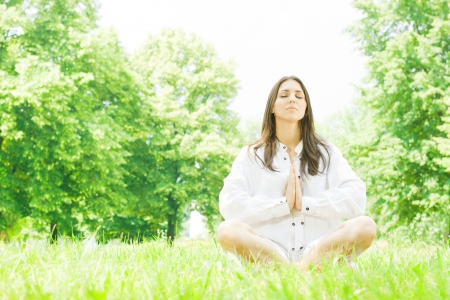 Beautiful young woman in meditation pose outdoors.