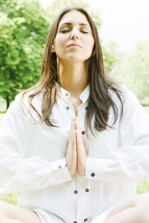 Beautiful young woman in meditation pose outdoors. photo