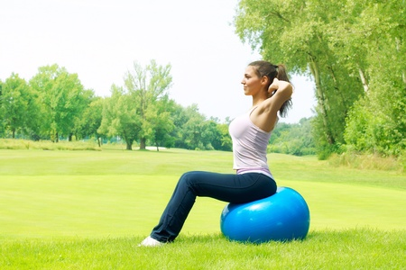 Fitness women exercising with pilates ball outdoors.