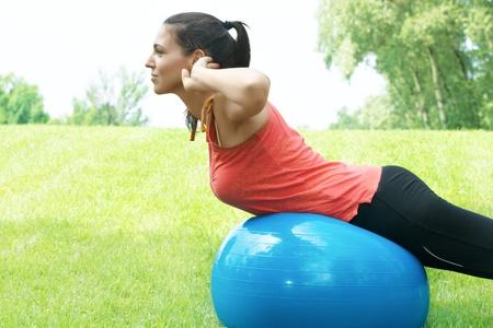 haciendo ejercicio: Chica de gimnasio haciendo ejercicio con pelota pilates al aire libre.