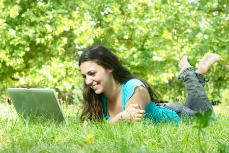Portrait of a cute young female lying on the grass in the park using a laptop. photo
