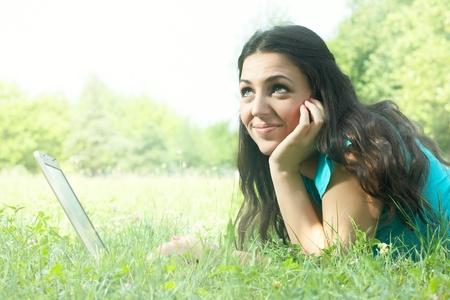 Thinking woman using laptop outdoors. Stock Photo - 9860047
