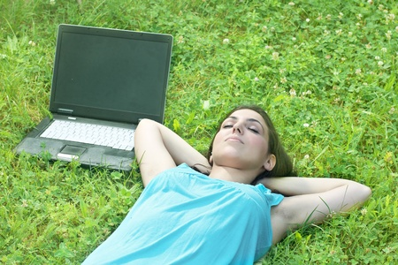Beautiful young woman relaxing on grass with laptop. photo