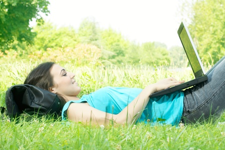 using a laptop: Happy student using laptop at the park.