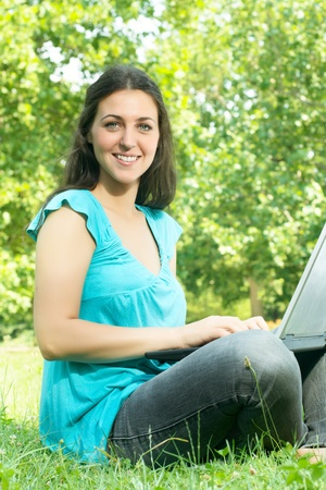 Portrait of beautiful young woman using laptop in the park. Stock Photo - 9860058