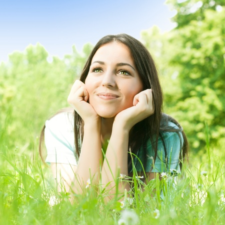Charming girl relaxing on green grass. Stock Photo