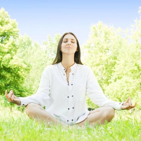 Beautiful young woman doing yoga in nature. Standard-Bild