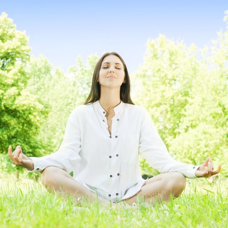 Beautiful young woman doing yoga in nature. Stock Photo