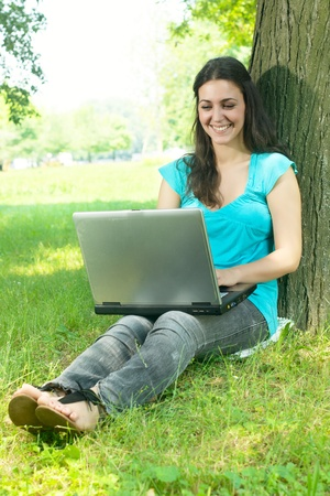 Beautiful happy young woman using laptop and leaning on tree. photo