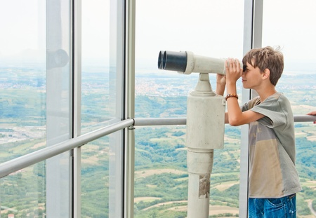 Young boy looking through tourist telescope , exploring landscape. photo