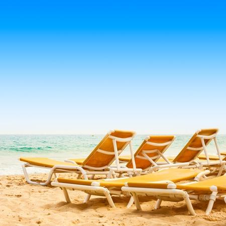 sunbeds: Sunbeds on the sandy beach with beautiful blue sky.