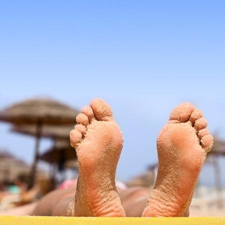 Closeup von Frau Fuß mit Sand am Strand. Standard-Bild