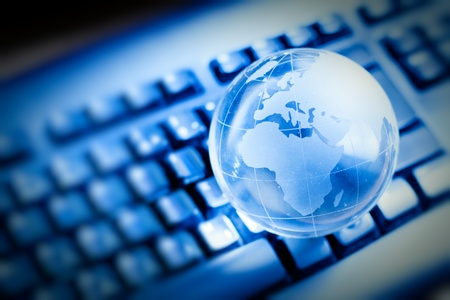 information society: Glass globe over keyboard , global communication concept.