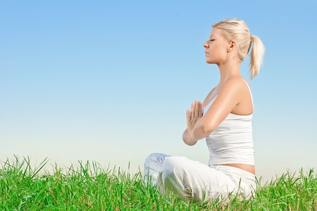 mind body: Young woman meditating outdoors with copyspace. Stock Photo