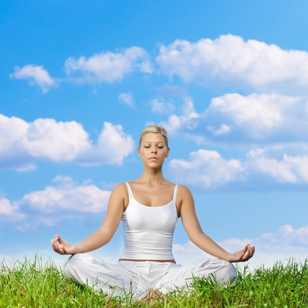 Young woman meditating on green grass with copyspace. photo