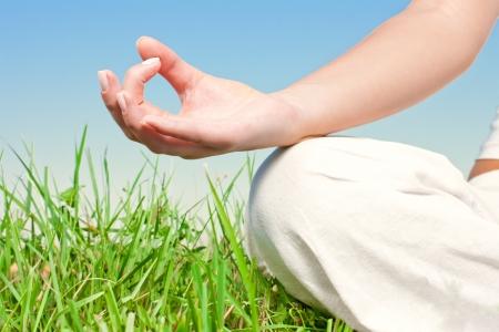 Primer plano de manos de la mujer en pose de yoga al aire libre.