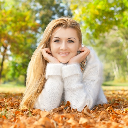 Portrait of smiling beautiful woman lying on a autumn leaves. photo