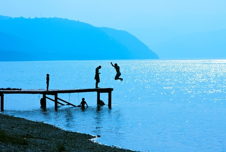 Silhouettes of kids who jump off dock on the lake.Blue toned. photo