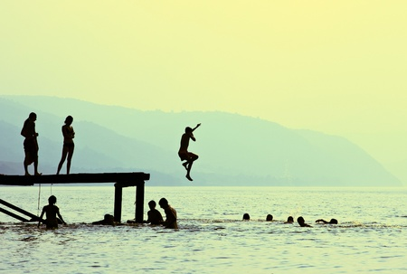fun: Silhouettes of kids who jump off dock on the lake at sunset. Stock Photo