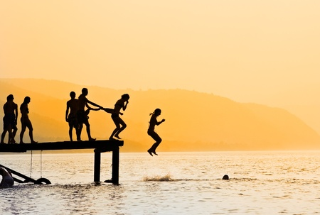 lake beach: Silhouettes of kids who jump off dock on the lake at sunset. Stock Photo