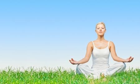 Jonge vrouw het beoefenen van yoga mediteren buiten met copyspace.