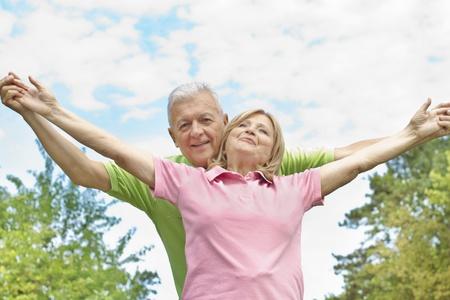 Gelukkig bejaarde echtpaar met opgeheven armen buiten.