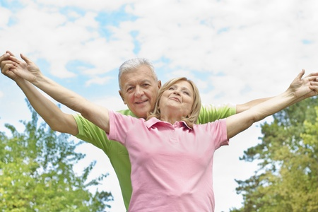 Happy elderly couple with raised arms outdoors. Stock Photo - 10570378