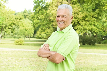 Portrait of successful senior man looking at camera outdoors.