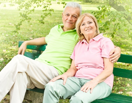 Happy senior couple relaxed on the park bench. Stock Photo - 10612935