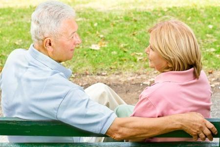 Achteraanzicht van oude paar zitten en praten over bankje. Stockfoto