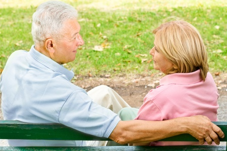 couple talking: Rear view of old couple sitting and talking on park bench.