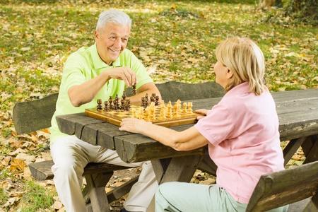 ajedrez: Feliz pareja de ancianos jugando al ajedrez en un banco del parque. Foto de archivo