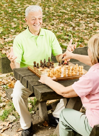 Happy senior couple playing chess on a park bench. photo